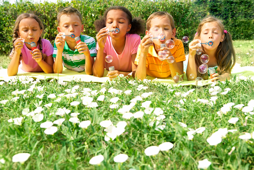 kids blowing bubbles on grass